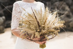 Wedding bouquet with dried flowers and spikelets Boho style in brides hands