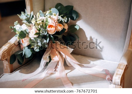 Wedding bouquet with white flowers, roses, greens and ribbons on the chair