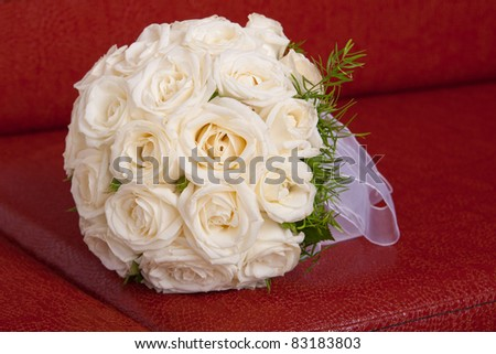 wedding bridal bouquet of white roses lay on a red couch