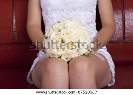 wedding bridal bouquet of white roses lay on his knees on a red couch