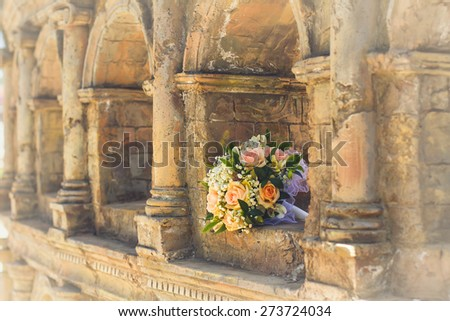 wedding bridal bouquet with white, peach and orange roses lies in the ancient building. Wedding theme