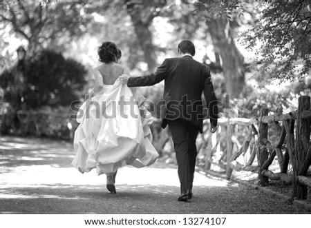 wedding - bride and groom walking in the park