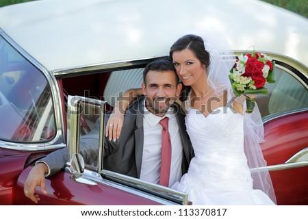 Wedding, bride and groom with a vintage car