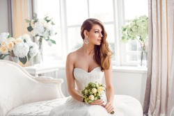 Wedding. Bride in beautiful dress sitting on sofa indoors in white studio interior like at home. Trendy wedding style shot. Young attractive caucasian brunette model like a bride against big window