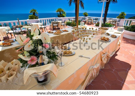 Wedding buffet with appetizer and champagne on a beautiful terrace overlooking the sea