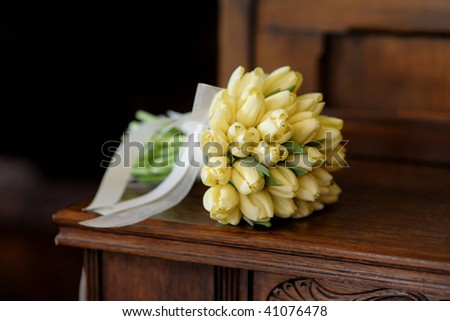 Wedding bunch of yellow tulips on the wooden bench