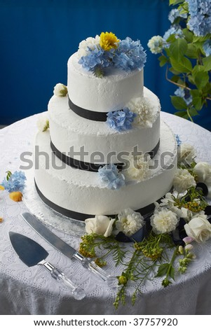 stock photo Wedding cake decorated with flowers on reception table