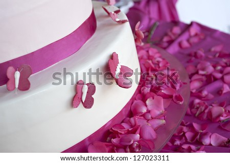 wedding cake decorated with rose petals and butterflies