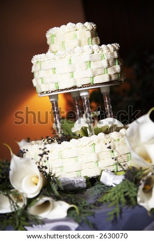 stock photo Wedding cake on a table with candles and white flowers