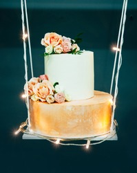 Wedding cake on decorative swing, decorated with fowers and luminous garland