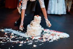 Wedding cake that fell to the floor. The waiter's hands collect it.