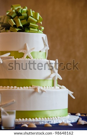wedding cake with a green bow and a seashell theme - stock photo