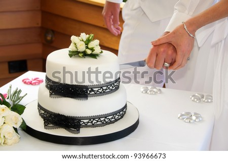 stock photo Wedding cake with black lace ribbon and white icing and little
