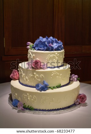 stock photo Wedding cake with flowers on reception table with dramatic