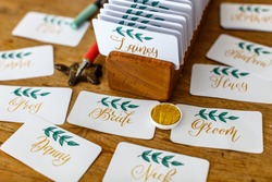 Wedding calligraphy - handwritten place cards with names. Golden writing with green flourish on white paper. Gold paint, nib pen, card holder.