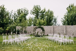 Wedding ceremony aisle with an arch made of flowers and greenery, with beautiful chairs on a green grass. Backyard wedding venue.