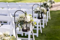 wedding ceremony aisle with chairs, lanterns, and flowers