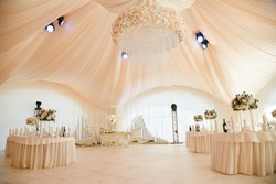 Wedding ceremony in a beautiful tent. Hall with dining tables decorated with bouquets of flowers.