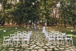 Wedding ceremony in the forest. Elegant decoration of a wedding ceremony outdoors. Outdoor wedding ceremony with beautiful white furniture. Wooden guest chairs.