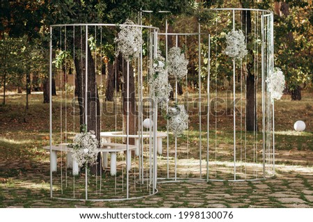 Wedding ceremony in the forest. Elegant decoration of a wedding ceremony outdoors. Outdoor wedding ceremony with beautiful white furniture. Wooden guest chairs.  Сток-фото ©