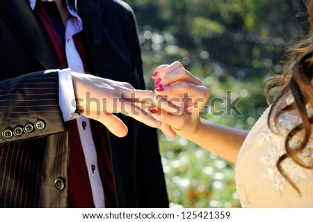 Wedding ceremony moment where the bride places the wedding ring on the groom finger