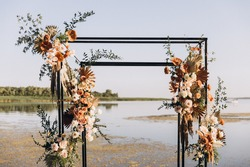 Wedding ceremony. On a green meadow on the seashore there is an arch decorated with flower arrangements, chairs for guests, candles and lamps