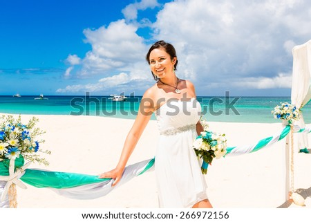 Wedding ceremony on a tropical beach in blue. Happy bride under the wedding arch decorated with flowers on tropical sand beach. Wedding and honeymoon concept.