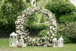Wedding ceremony. Very beautiful and stylish wedding arch, decorated with various fresh flowers, standing in the garden. Wedding day. Fresh flowers decorations, Peony weddng.