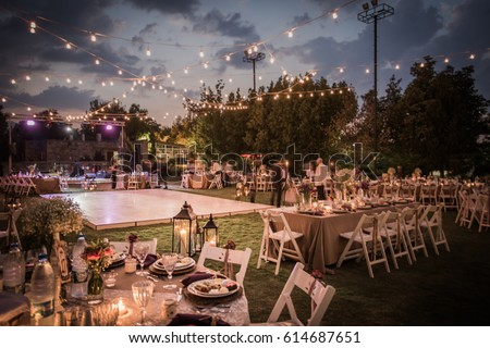 Wedding Ceremony with flowers outside in the garden with hanging lights #614687651