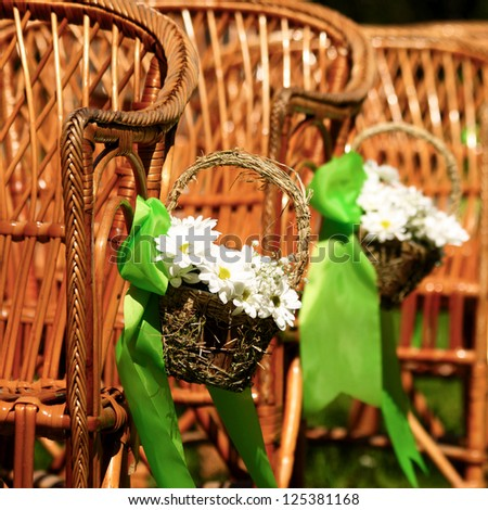 Wedding chairs with chamomile flowers and green details from ceremony and reception