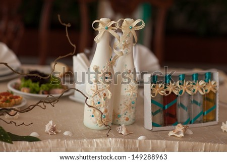 Wedding champagne decoration with seashells starfish at royal wedding dinner. Wedding table decoration at tropical bridal table. thailand wedding. alcoholic drink decorated sea style. wedding decor