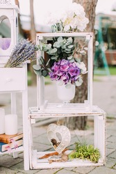 Wedding composition of the white wooden crates with vase of colourful flowers in it. The crates are decorated with handmade hearts.
