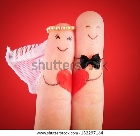 wedding concept - newlyweds painted at fingers against red background