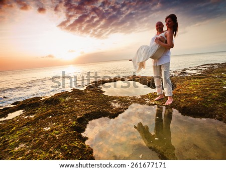 wedding couple at Hawaii, husband holding on hands his bride #261677171