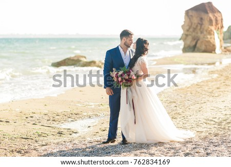 wedding couple. Beautiful bride and groom. Just merried. Close up. Happy bride and groom on their wedding hugging. Groom and Bride on the beach near the sea. wedding dress.  Foto stock ©