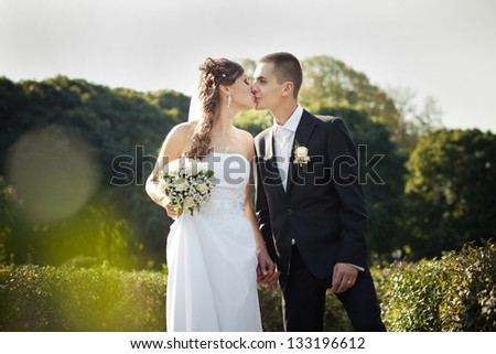 wedding couple, beautiful young bride and groom walk in the park outdoors holding hands and smiling