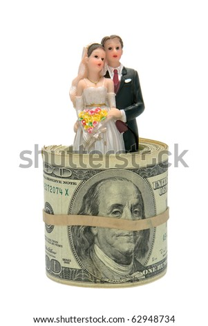 Wedding couple bride and groom cake topper figurine inside a roll of US dollar banknote bills as metaphor for the high cost of getting married and marriage isolated on white