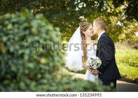 wedding couple -  bride and groom standing in a park outdoors holding hands and smiling