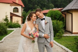 Wedding couple. Happy bride with wedding bouquet holds the groom's arm. Stylish newlywed couple. Marriage concept. Rustic wedding