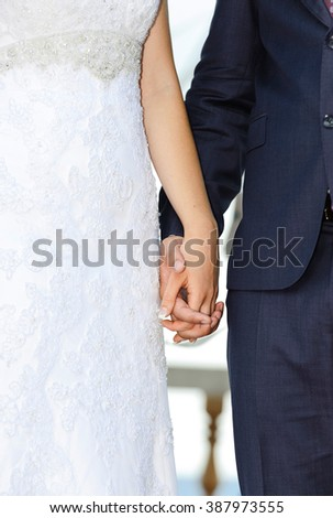 Wedding couple holding hands. Bride and groom holding hands in wedding ceremony. #387973555