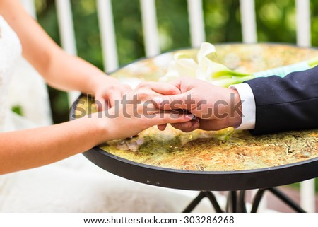 Wedding couple holding hands.  hands with wedding rings