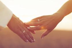 Wedding couple holding hands on sunset background