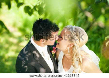 wedding couple hugging and kissing in a private moment of joy