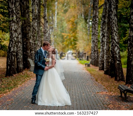 wedding couple hugging and kissing in a private moment of joy on a sunny autumn day