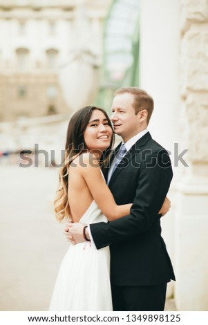 Wedding couple hugging and standing with her back outdoors near the pool. Happy bride and groom in love on their honeymoon. Woman in an elegant dress a man in the suit #1349898125