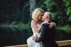 Wedding couple in a forest in the mountains at sunset. Romantic wedding couple in love standing on the stony shore. Stylish groom kissing gorgeous bride in sun light, perfect moment.