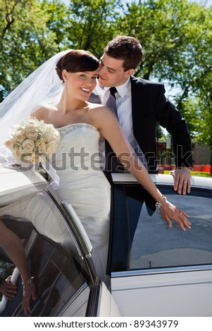 Wedding couple in Limo, groom about to kiss bride