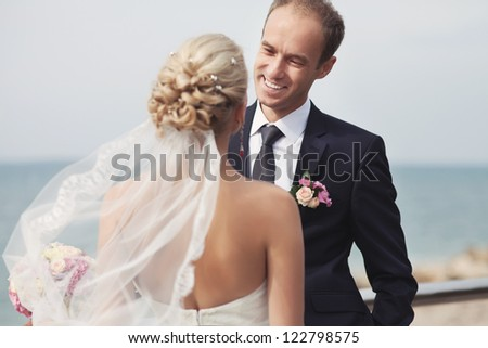 wedding: couple in love bride and groom together in bridal summer day enjoy a moment of happiness and love. Beautiful happy newlywed outdoors. handsome man and alluring woman in white dress on nature