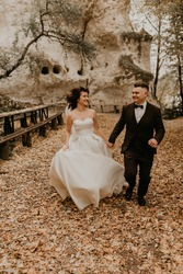 wedding couple in love man and woman run happy in autumn forest background of stone rocks. groom in suit and bride in dress with long veil on short hair sports shoes outdoors. rock monastery in bakota