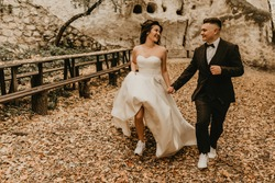 wedding couple in love man and woman run happy in autumn forest background of stone rocks. groom in suit and bride in dress  sports shoes outdoors. rock monastery in bakota